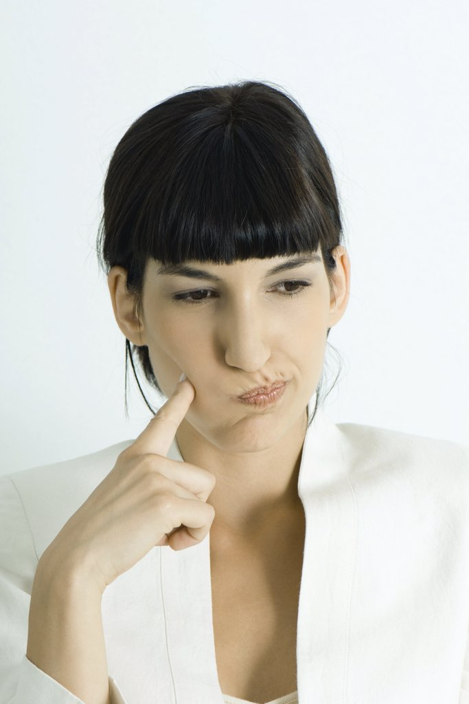 Young businesswoman puffing cheeks out, holding finger to cheek, looking away, portrait : Stock Photo