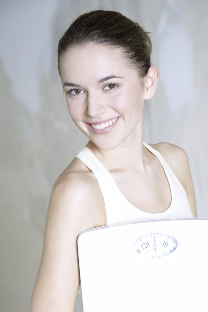 Young woman holding bathroom scale, smiling at camera, portrait : Stock Photo