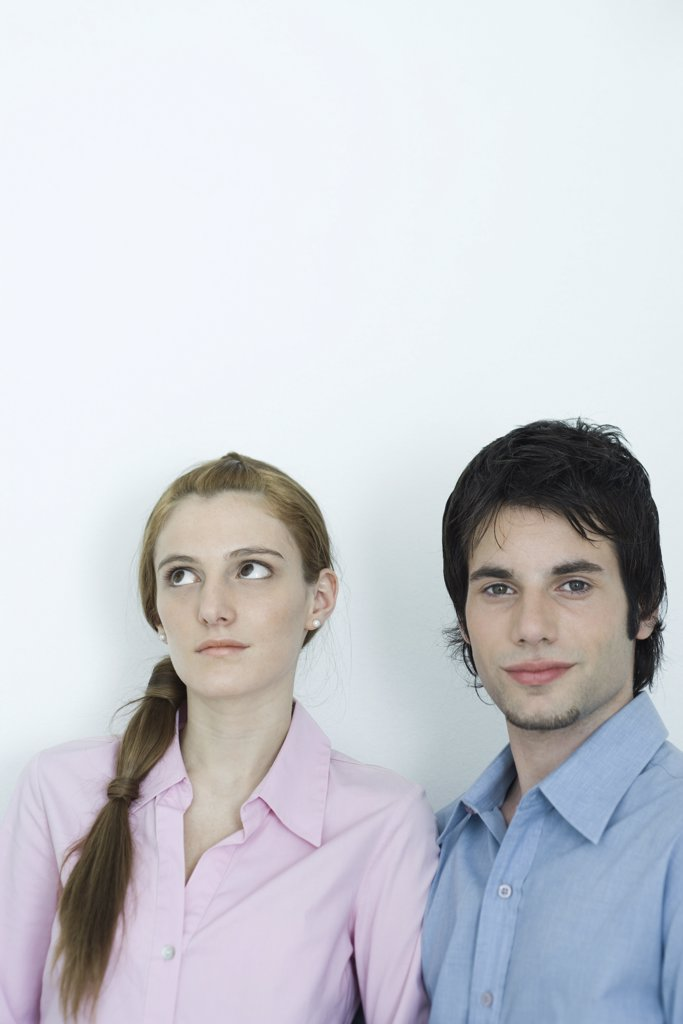 Young couple, man looking at camera while woman looks away, portrait : Stock Photo