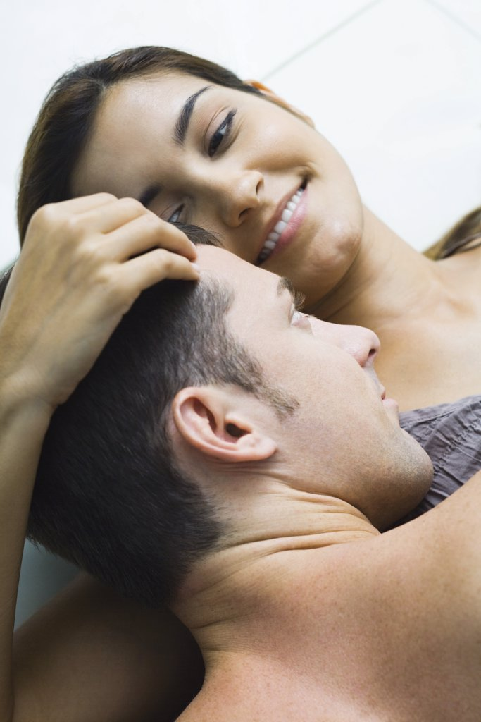 Man lying on top of woman, woman holding his head, smiling, high angle view : Stock Photo
