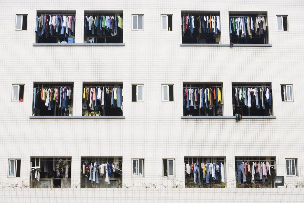 Laundry hanging to dry in balconies of apartment building : Stock Photo