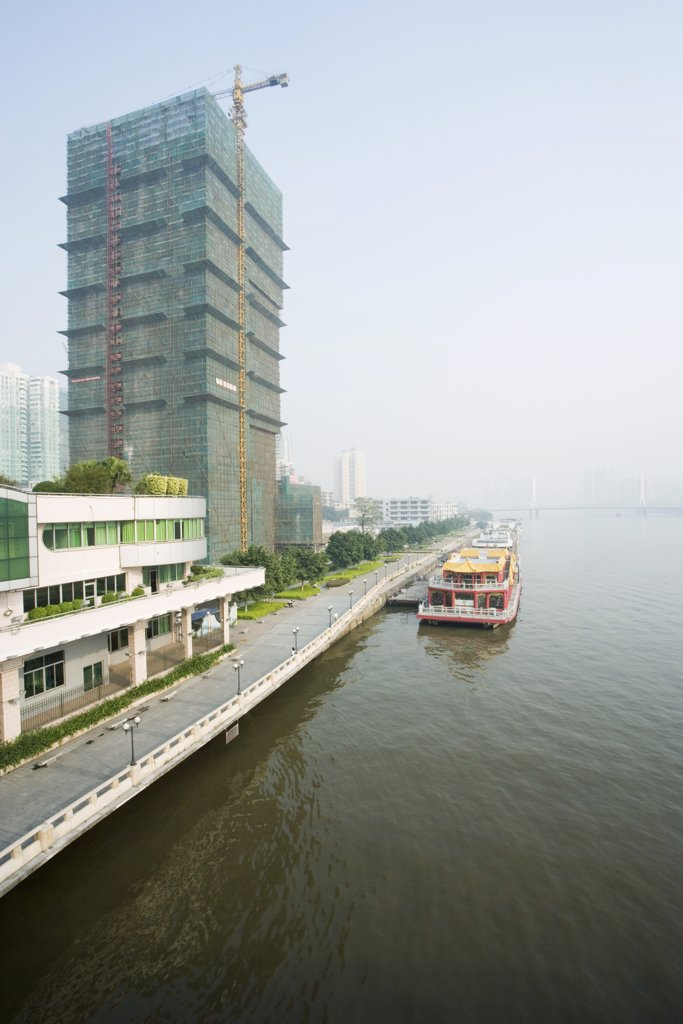 China, Guangdong Province, barge parked along quay near high rise under construction : Stock Photo