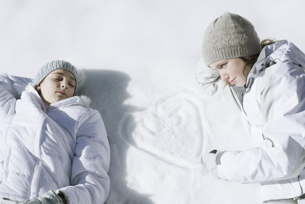 Stock Photo: 1569R-9028598 Teenage girls lying on snow, one drawing heart with initials in snow