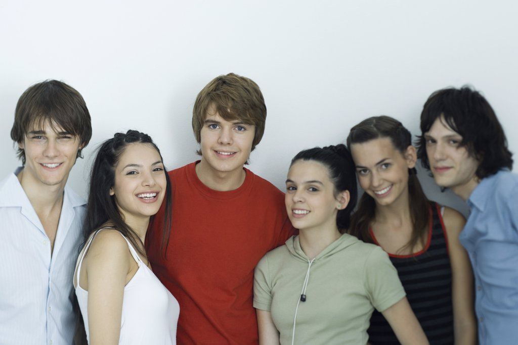 Group of young friends posing for photo, smiling at camera, waist up : Stock Photo