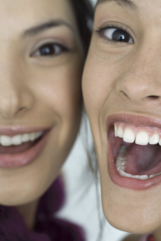 Two young female friends smiling with mouths wide open, looking at camera, extreme close-up of faces, cropped : Stock Photo
