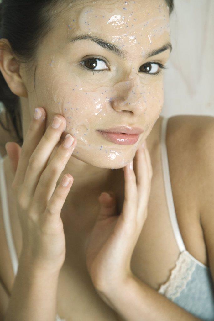 Young woman putting exfoliant mask on face, smiling at camera : Stock Photo