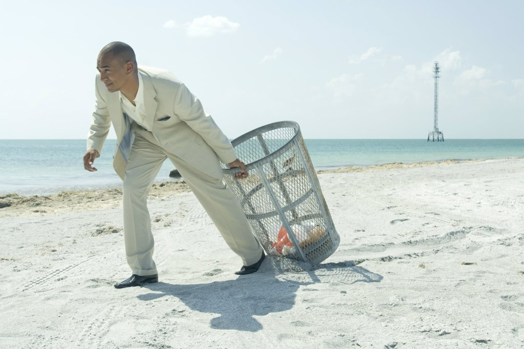 Stock Photo: 1569R-9028996 Man in suit pulling garbage can across sunny beach, full length