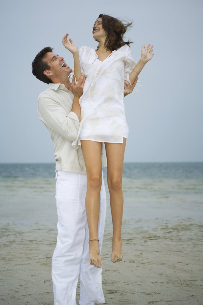 On beach, man holding young female companion up in air, full length : Stock Photo