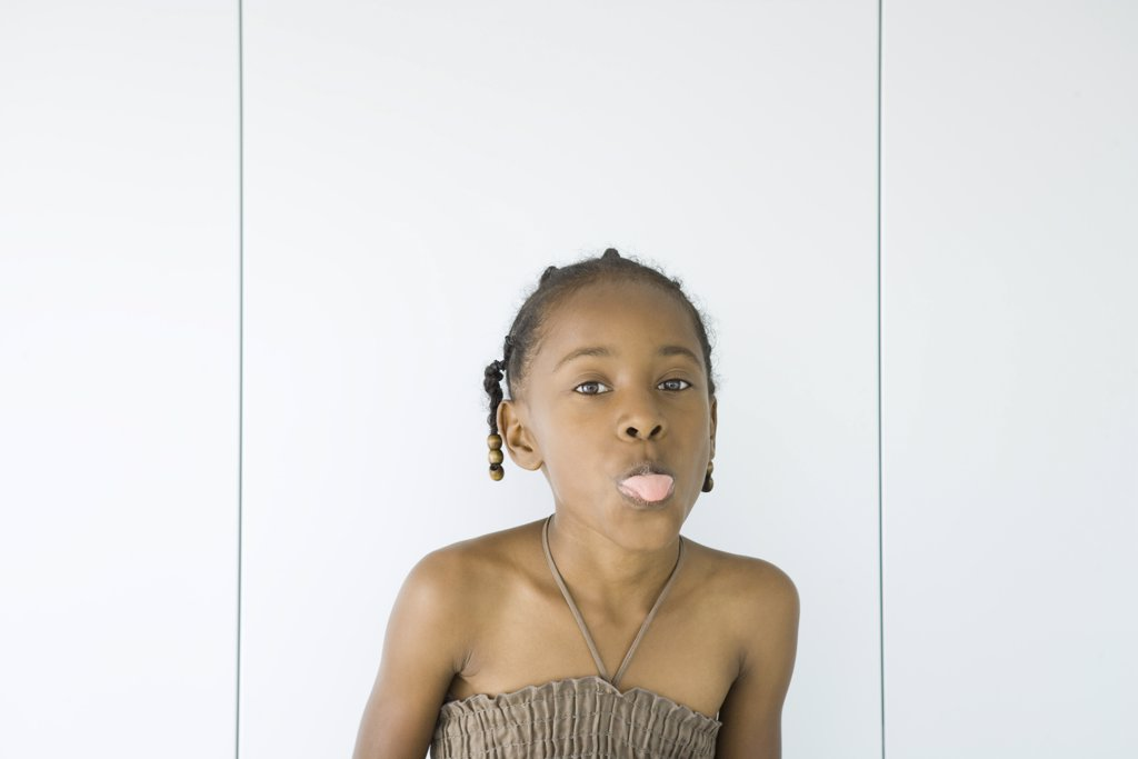 Little girl wearing halter top, sticking out tongue at camera, portrait : Stock Photo