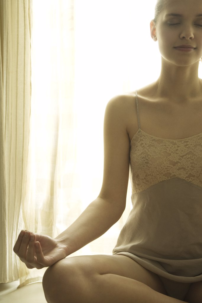 Teenage girl in front of window sitting in lotus position, eyes closed, cropped view : Stock Photo