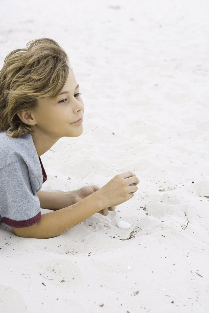 Boy lying in sand, looking away, side view : Stock Photo