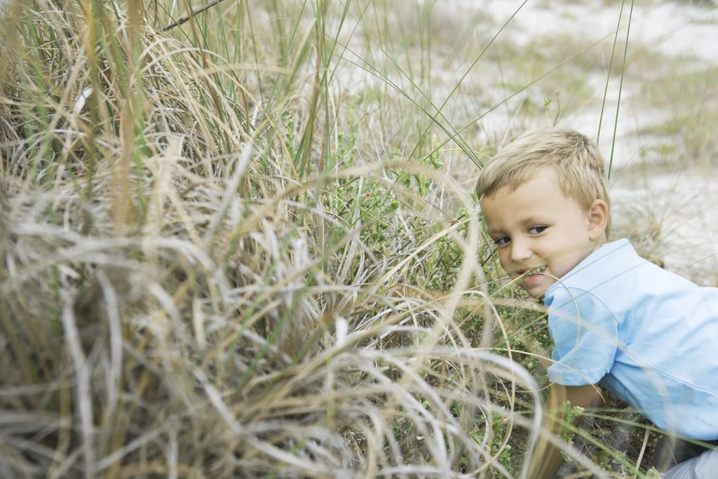 Stock Photo: 1569R-9029570 Young boy crouching in tall grass, looking away