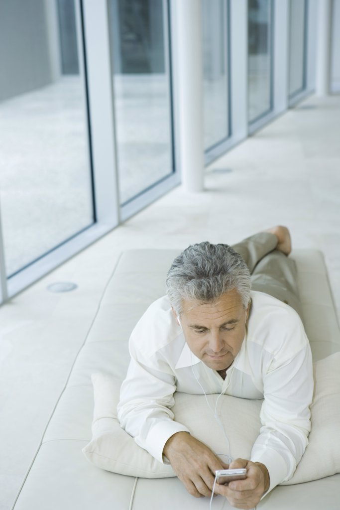 Mature man lying on chaise longue listening to mp3 player, high angle view : Stock Photo