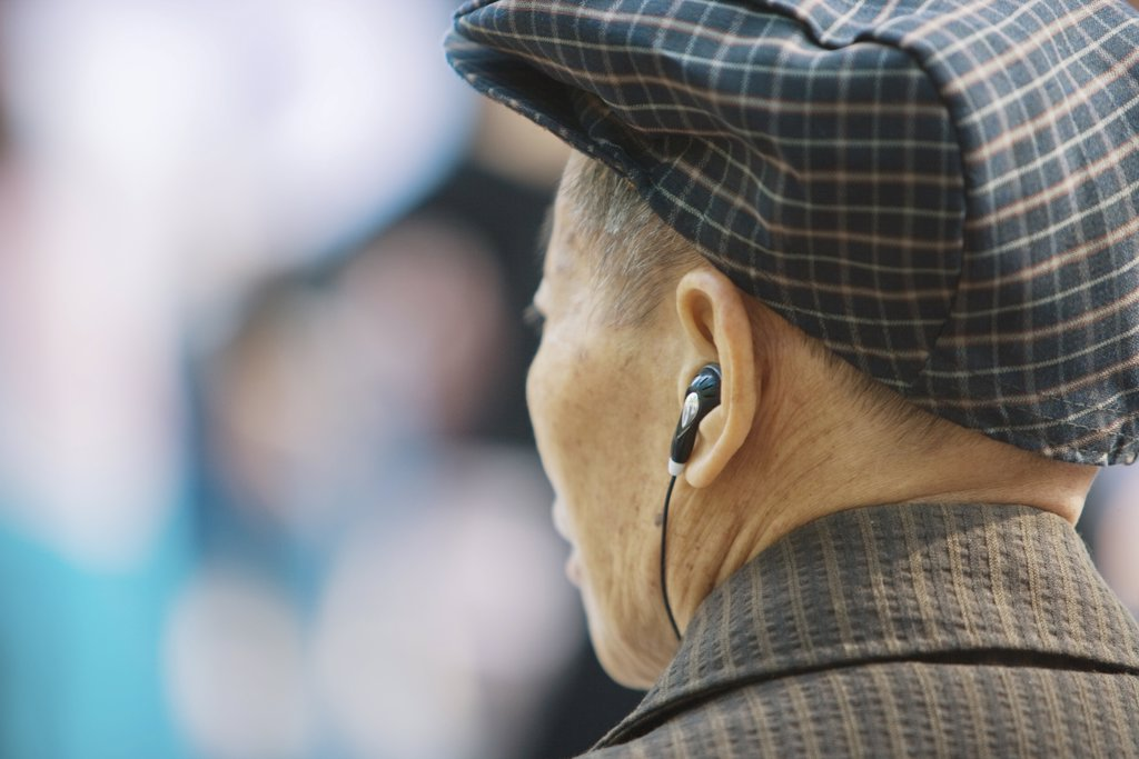 Stock Photo: 1569R-9029941 Senior man listening to earphones, rear view, head and shoulders