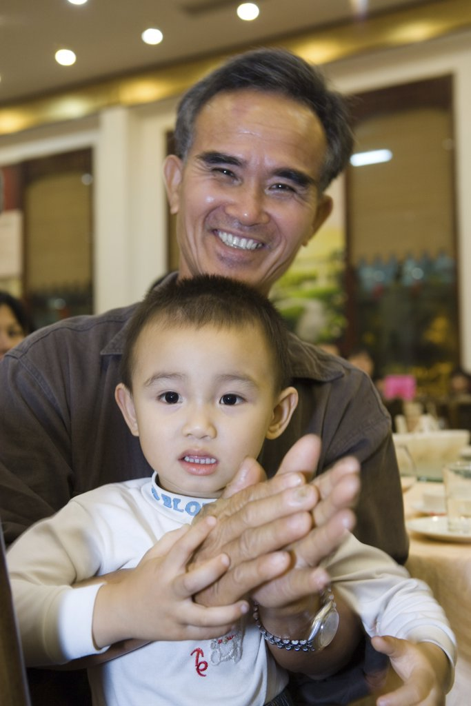 Stock Photo: 1569R-9030047 Man holding toddler on lap, clapping, smiling at camera