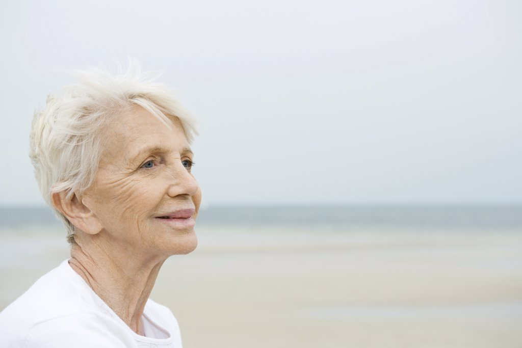 Stock Photo: 1569R-9030236 Senior woman smiling, looking away, beach in background