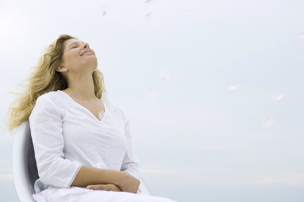 Woman sitting with eyes closed and head back, smiling, sky in background, low angle view : Stock Photo