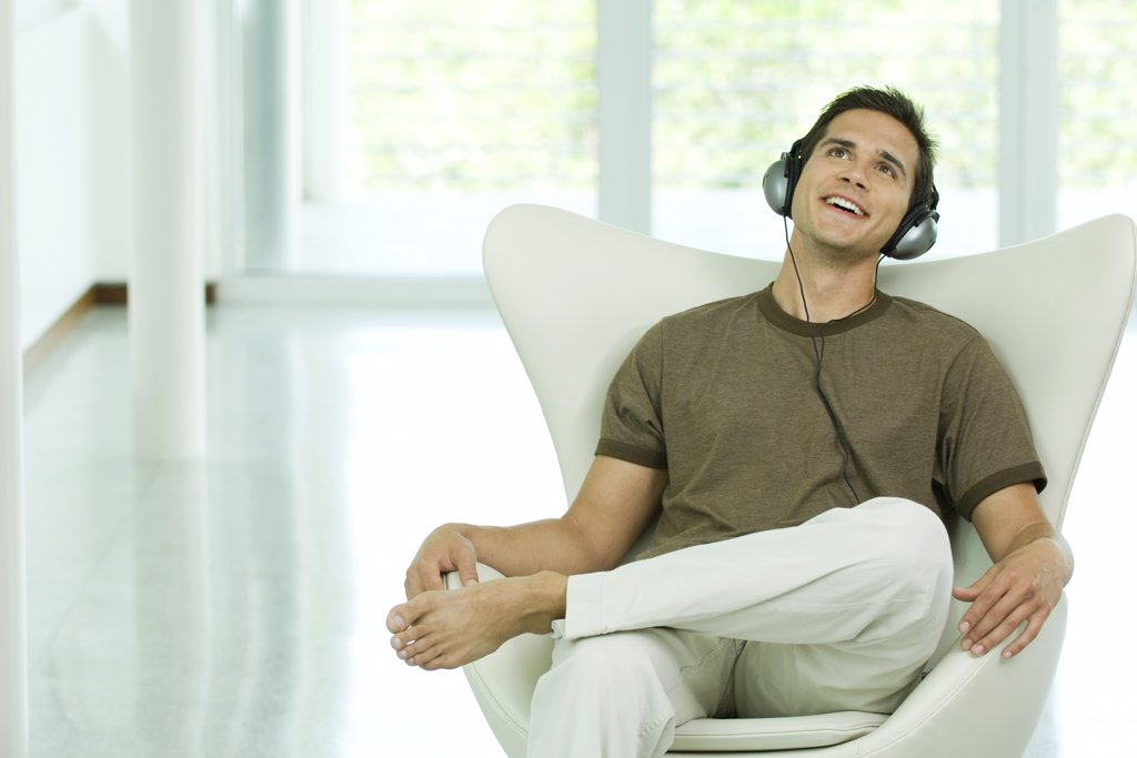 Young man sitting in chair listening to headphones, smiling : Stock Photo