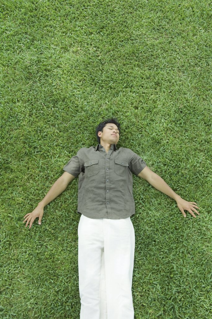 Man lying on back in grass, eyes closed, full length : Stock Photo