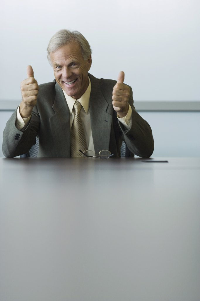 Businessman giving two thumbs up, smiling at camera : Stock Photo