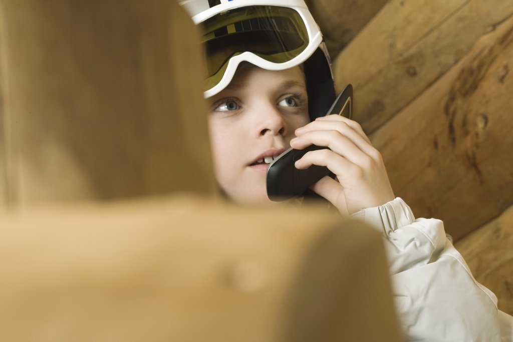 Boy wearing ski goggles, using cell phone, cropped view : Stock Photo