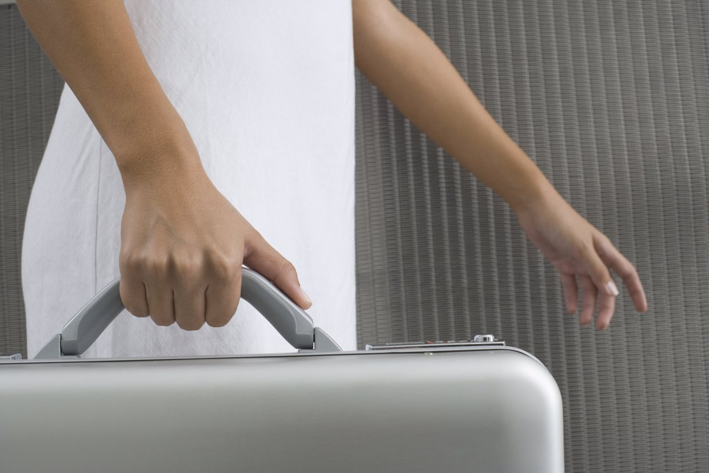 Woman walking and carrying briefcase, cropped view of hands : Stock Photo