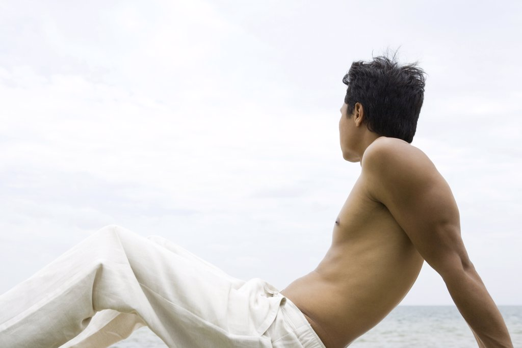 Man sitting and looking at view, side view : Stock Photo