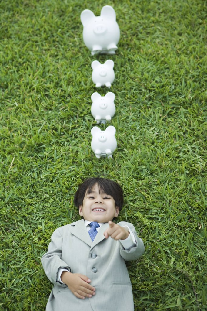 Boy dressed in suit lying on grass, laughing and pointing at camera, piggy banks above head : Stock Photo