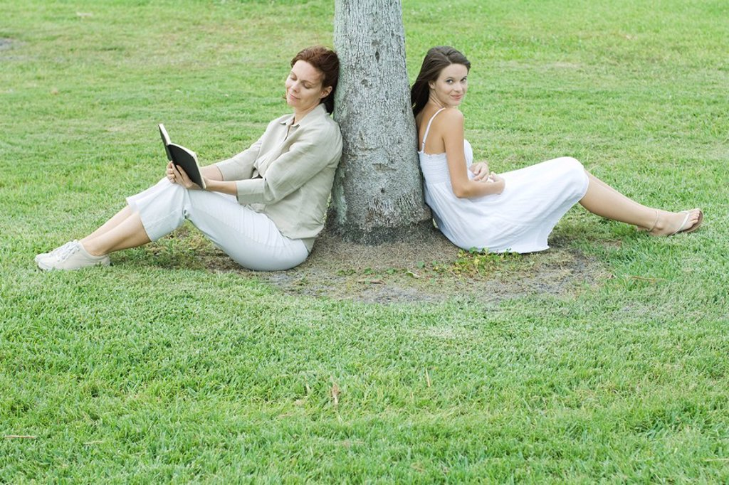 Mother and daughter leaning against tree trunk, woman reading book, teen girl smiling at camera : Stock Photo