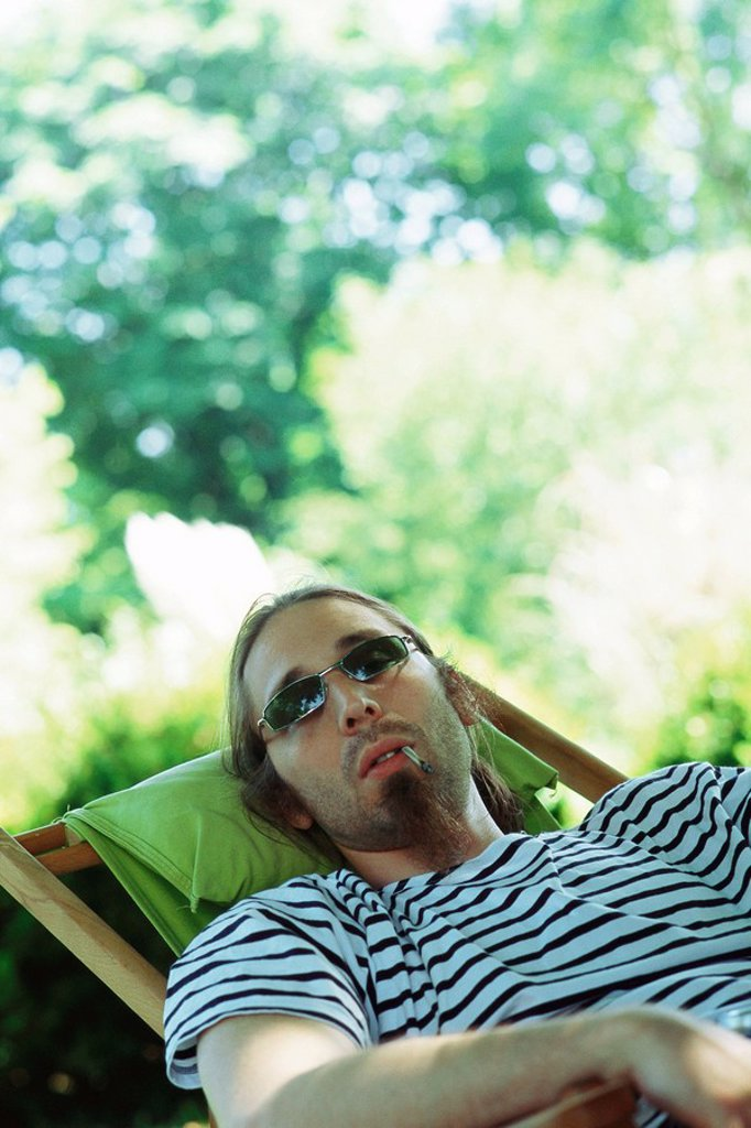 Man wearing sunglasses reclining in chair, smoking hand-rolled cigarette : Stock Photo