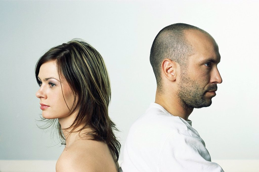 Stock Photo: 1569R-9031542 Couple back to back, both looking away, side view