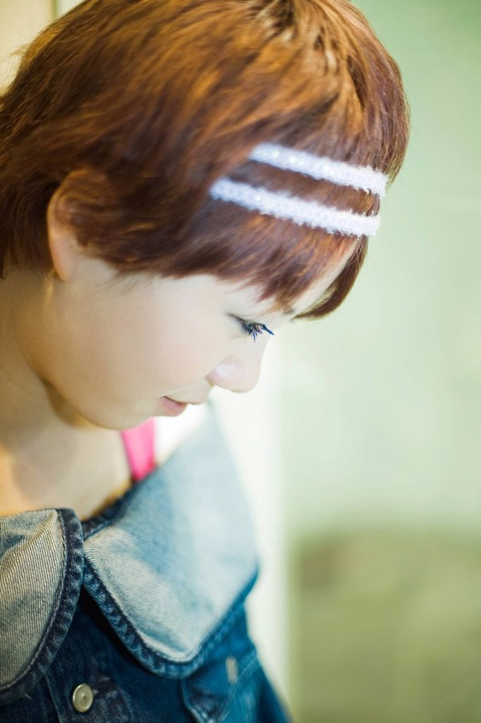 Stock Photo: 1569R-9031562 Young woman looking down, head down, side view