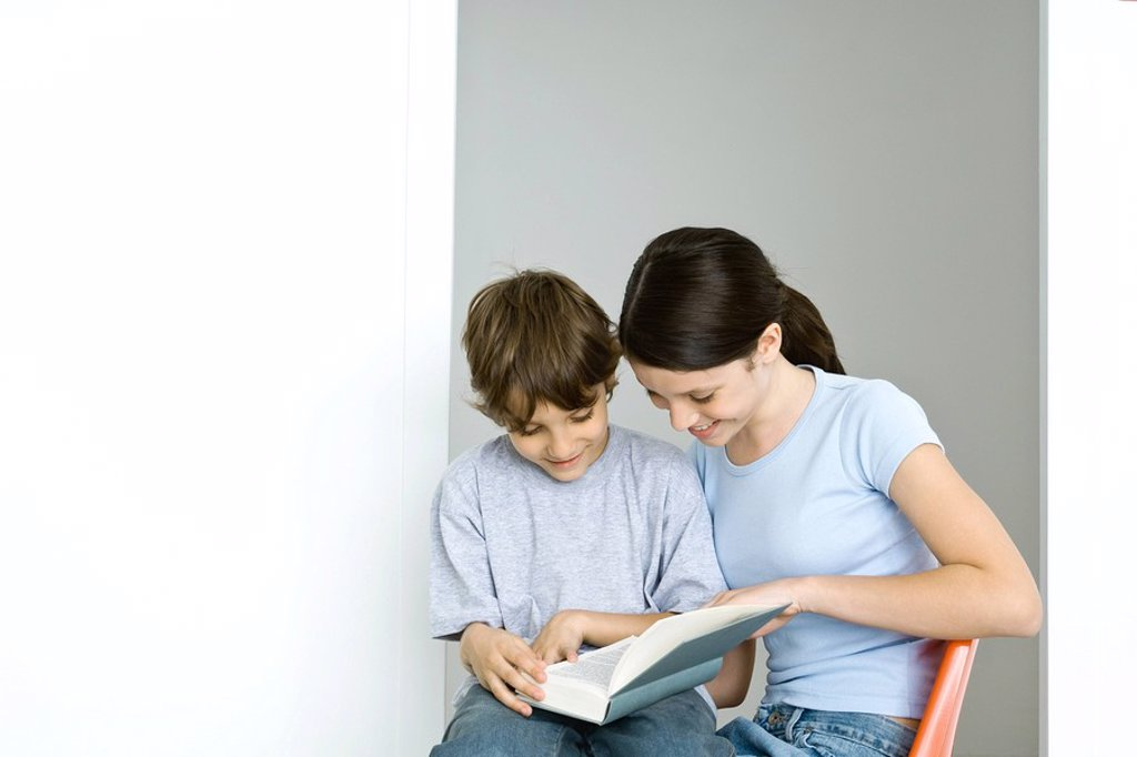 Brother and sister sitting, reading book together, both smiling : Stock Photo