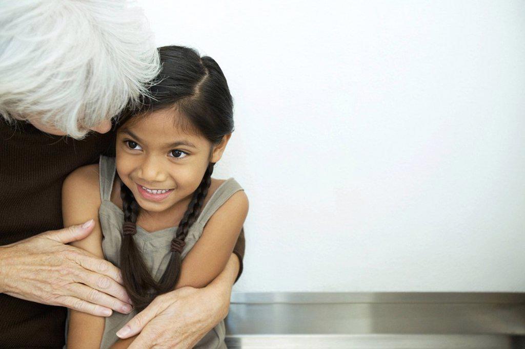 Stock Photo: 1569R-9031928 Grandmother embracing granddaughter, close-up