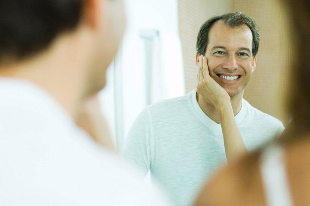 Stock Photo: 1569R-9032068 Man with wife´s hand on his cheek, smiling at reflection in mirror, over the shoulder view