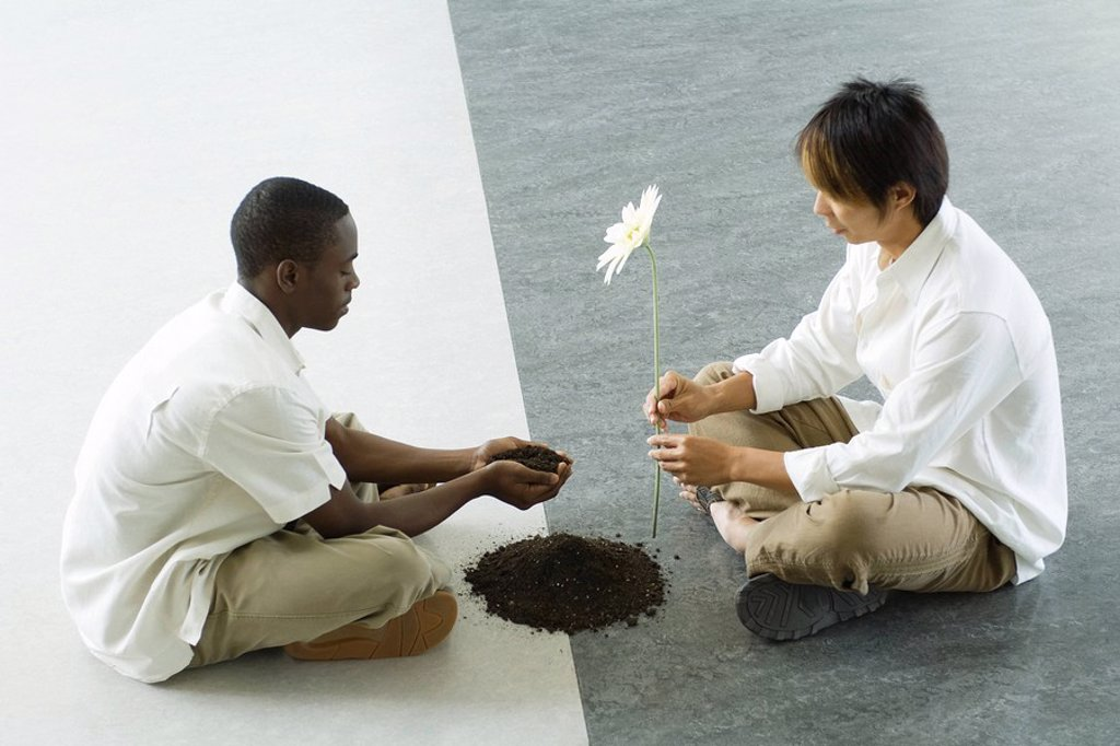 Two males sitting face to face on ground, one holding out handful of soil, the other holding out a flower : Stock Photo