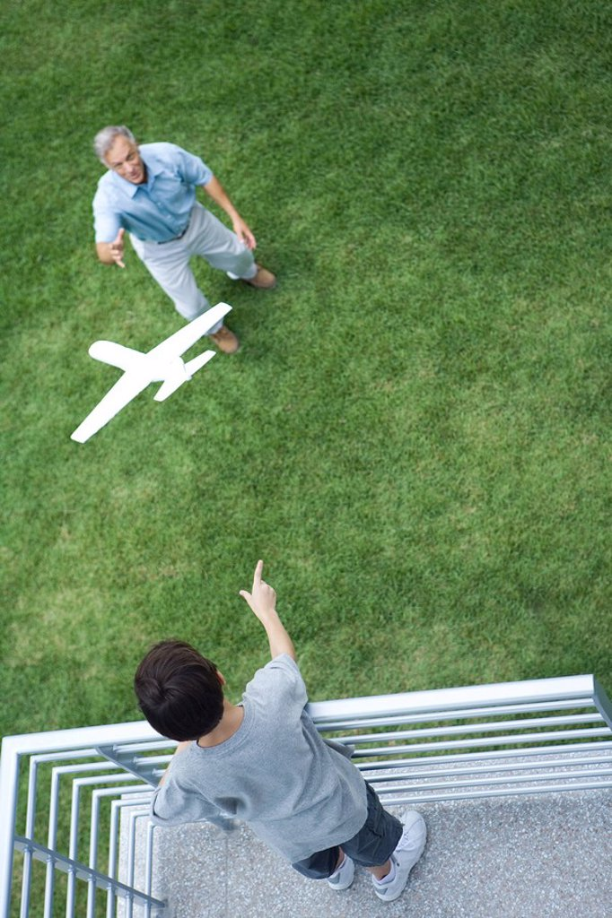 Boy standing on balcony, throwing toy airplane to grandfather standing below, high angle view : Stock Photo