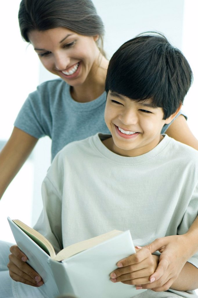 Teenage girl helping boy read book : Stock Photo