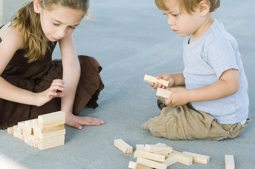 Stock Photo: 1569R-9032421 Brother and sister sitting on the ground, playing with building blocks together