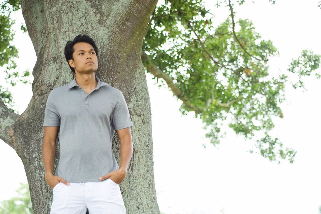 Man leaning against tree, looking away, three quarter length : Stock Photo