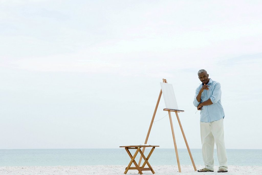 Stock Photo: 1569R-9032652 Senior man standing next to blank canvas at the beach, holding paint brushes, smiling at camera
