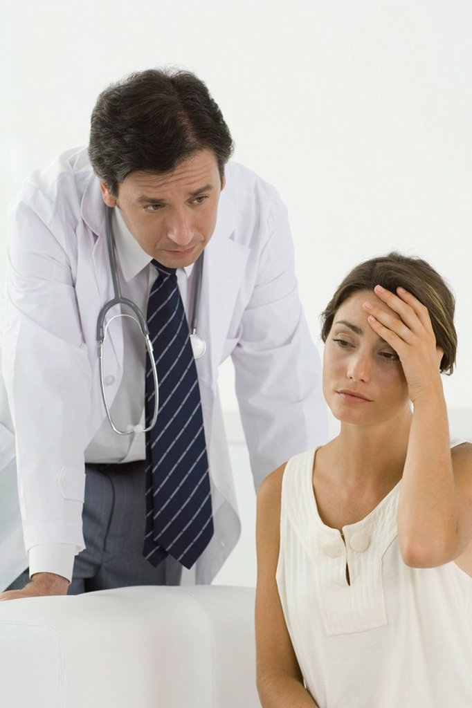 Woman sitting, holding head, doctor leaning over behind her : Stock Photo