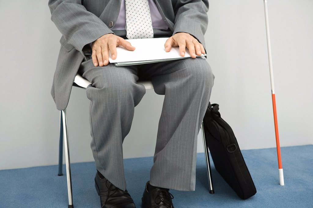 Visually impaired man sitting in chair, holding documents on lap, cropped view, chest down : Stock Photo
