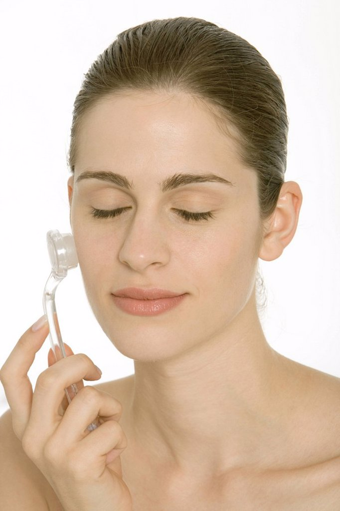 Stock Photo: 1569R-9033366 Woman using exfoliator brush on face