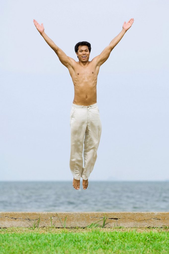 Man jumping in the air with arms raised, smiling at camera, the sea in background : Stock Photo