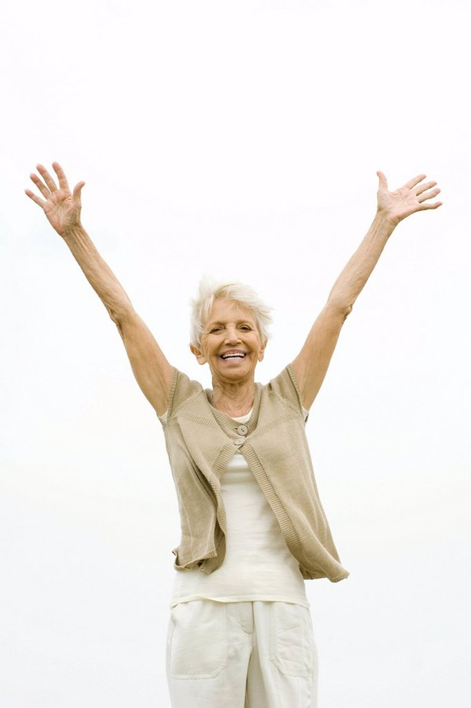 Senior woman standing outdoors with arms raised in the air, smiling at camera : Stock Photo