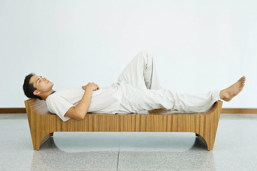 Stock Photo: 1569R-9033488 Man lying on bench with eyes closed, side view