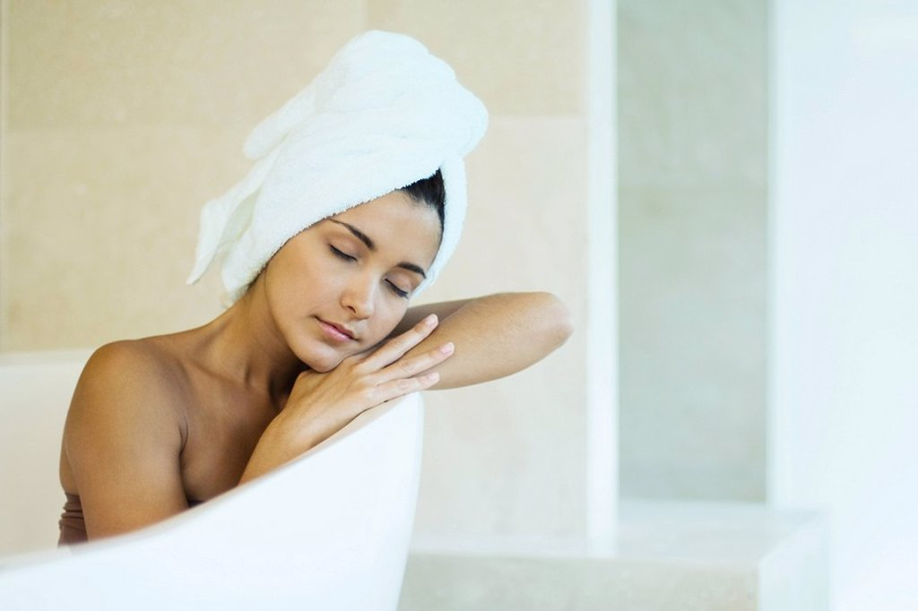 Woman sitting in bathtub with towel wrapped around hair, head resting on arms, eyes closed : Stock Photo