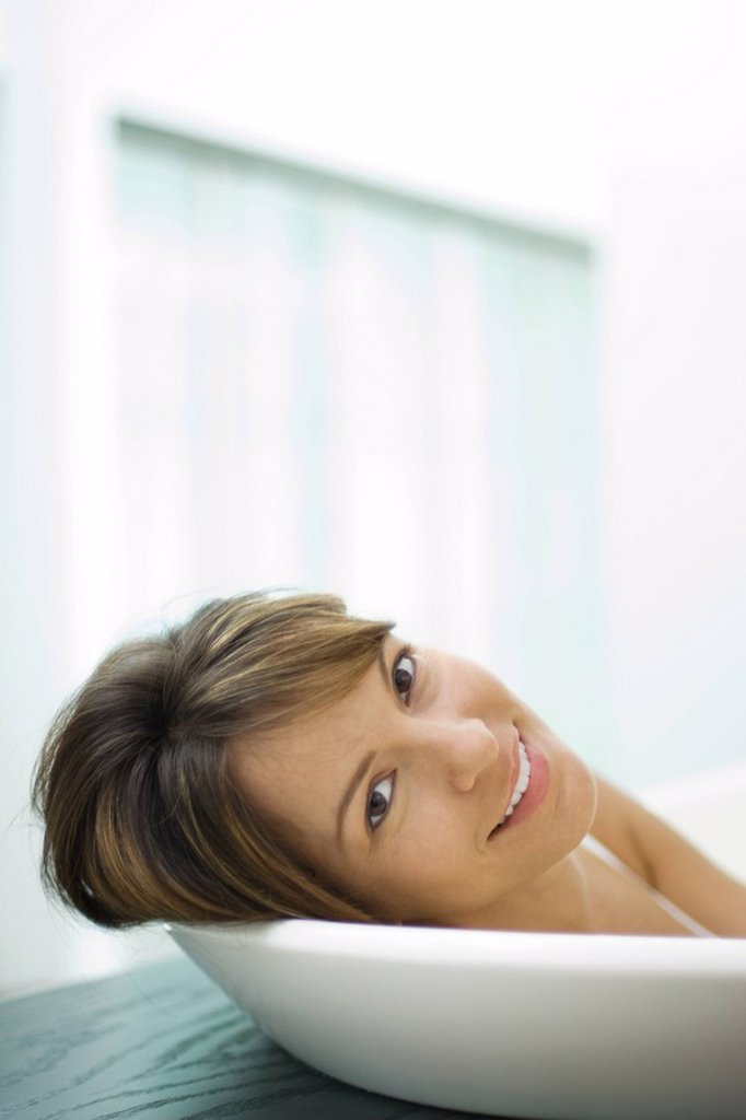 Woman leaning head against side of bathtub, smiling at camera, close-up : Stock Photo