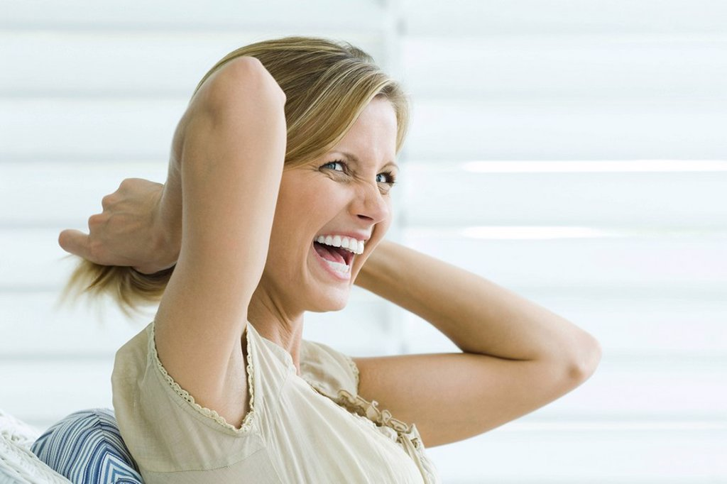 Woman pulling hair back with hands, laughing, side view : Stock Photo